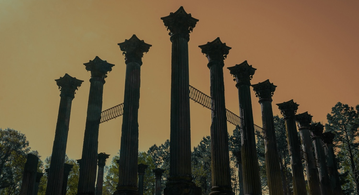 View of pillars reaching into the orange sky at dusk