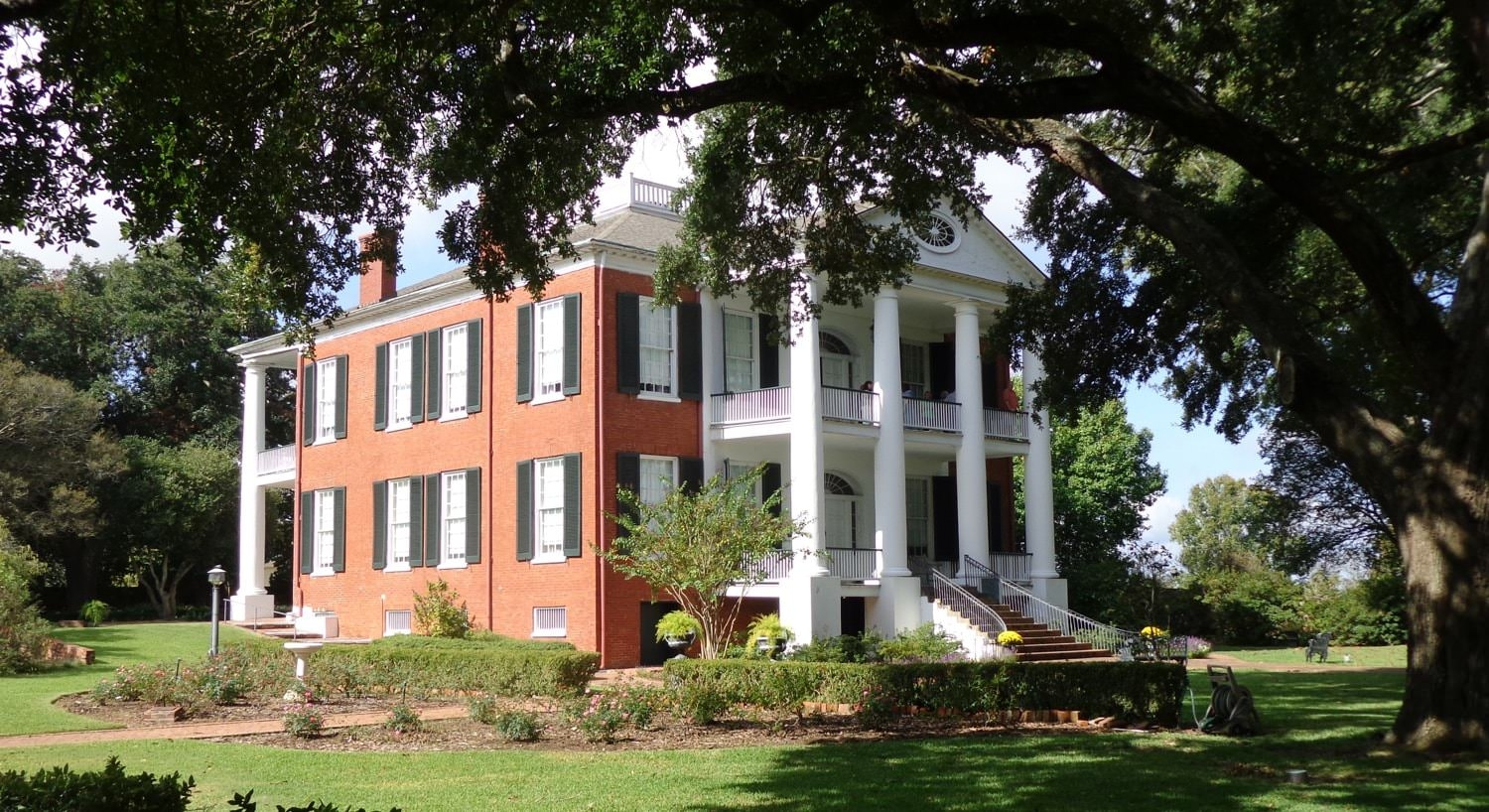 View of a red brick b&b with white pillars and many windows with black shutters overlooking bright green lawn