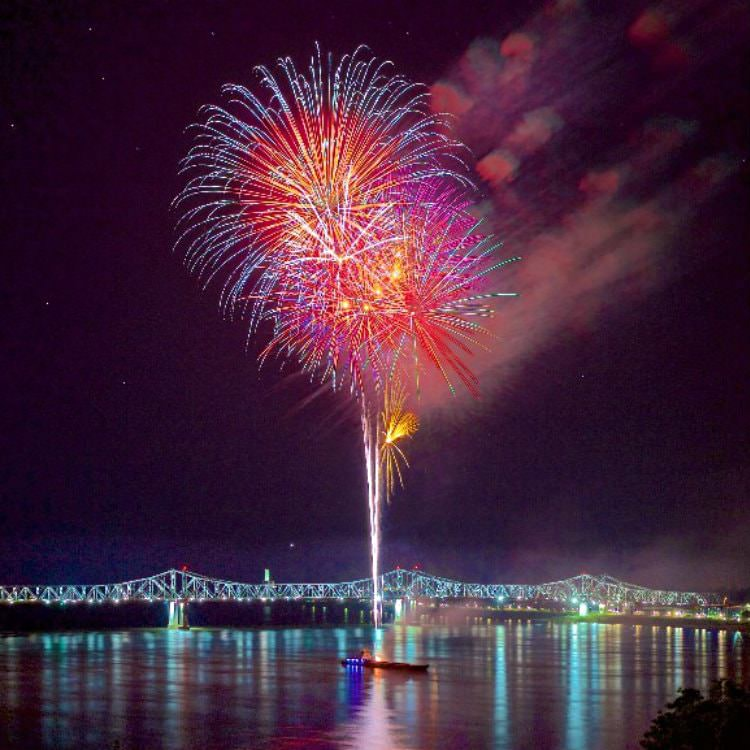 A rainbow colored fireworks display shooting from a small boat over the water with the bridge in the background well-lit at night