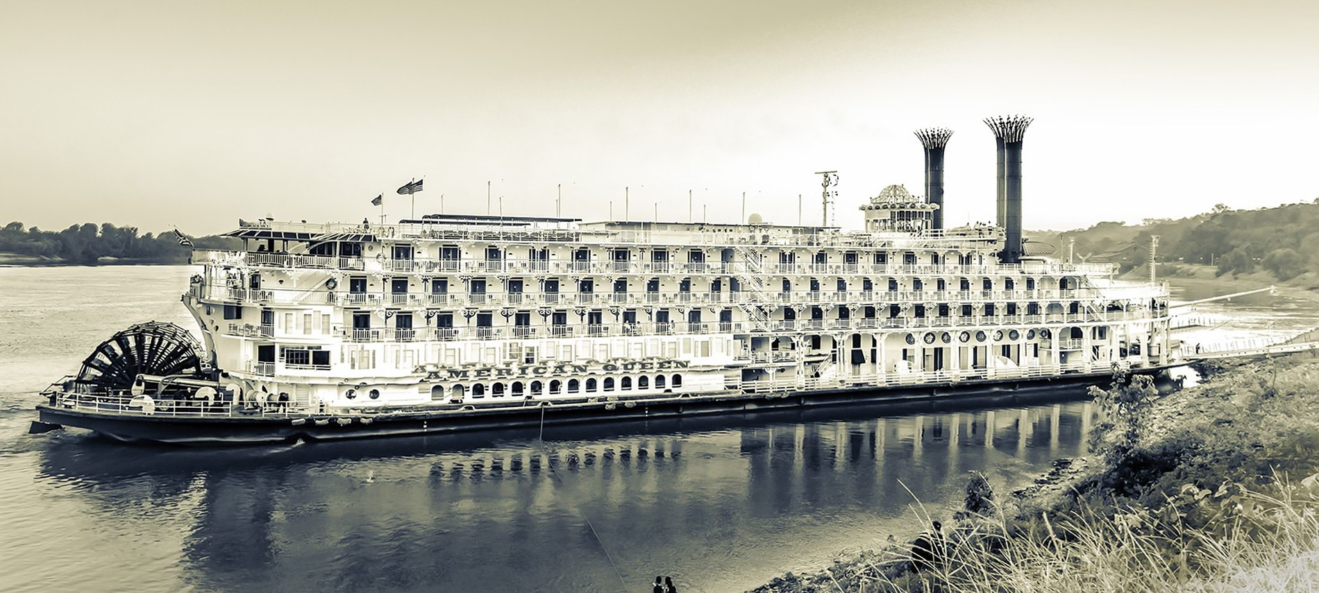 Large, intricate ship sitting on the water with the name American Queen in sepia tones