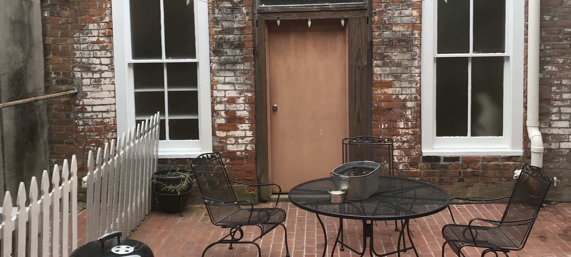 Porch area in front of b&b with rustic brick siding and tan door, black metal patio furniture, brick flooring, and white fencing