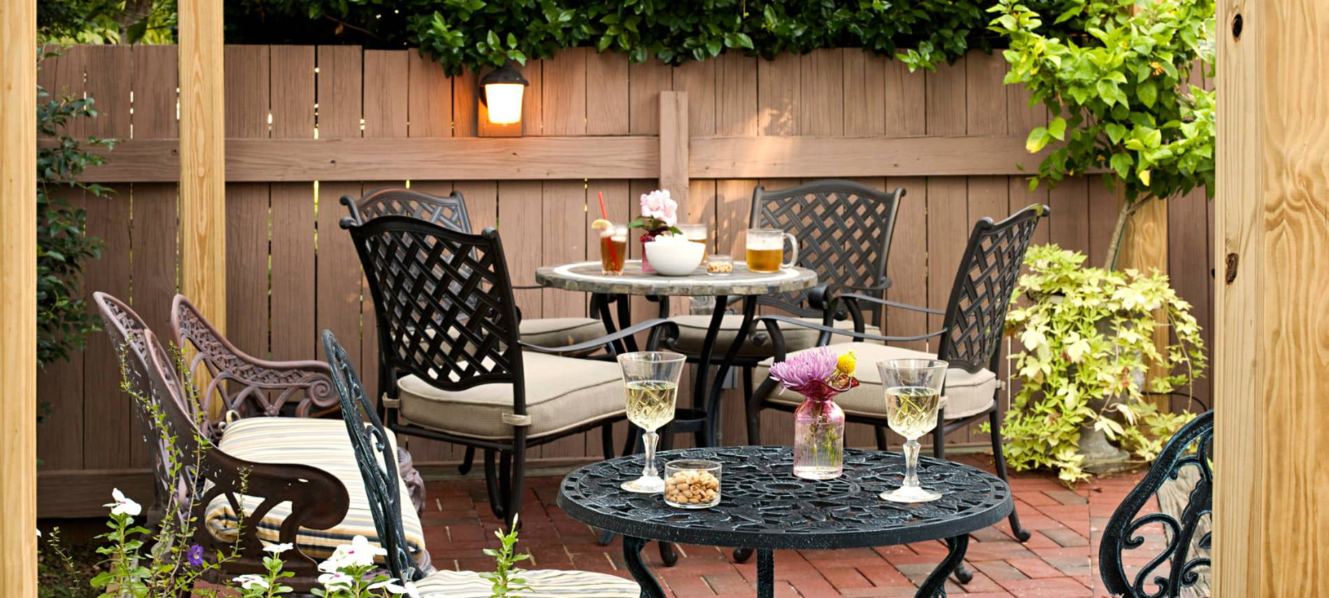 Porch area decorated with dark cast iron furniture, red brick flooring, light brown fencing, and beige cushions; tables coveredin delicious drinks and snacks