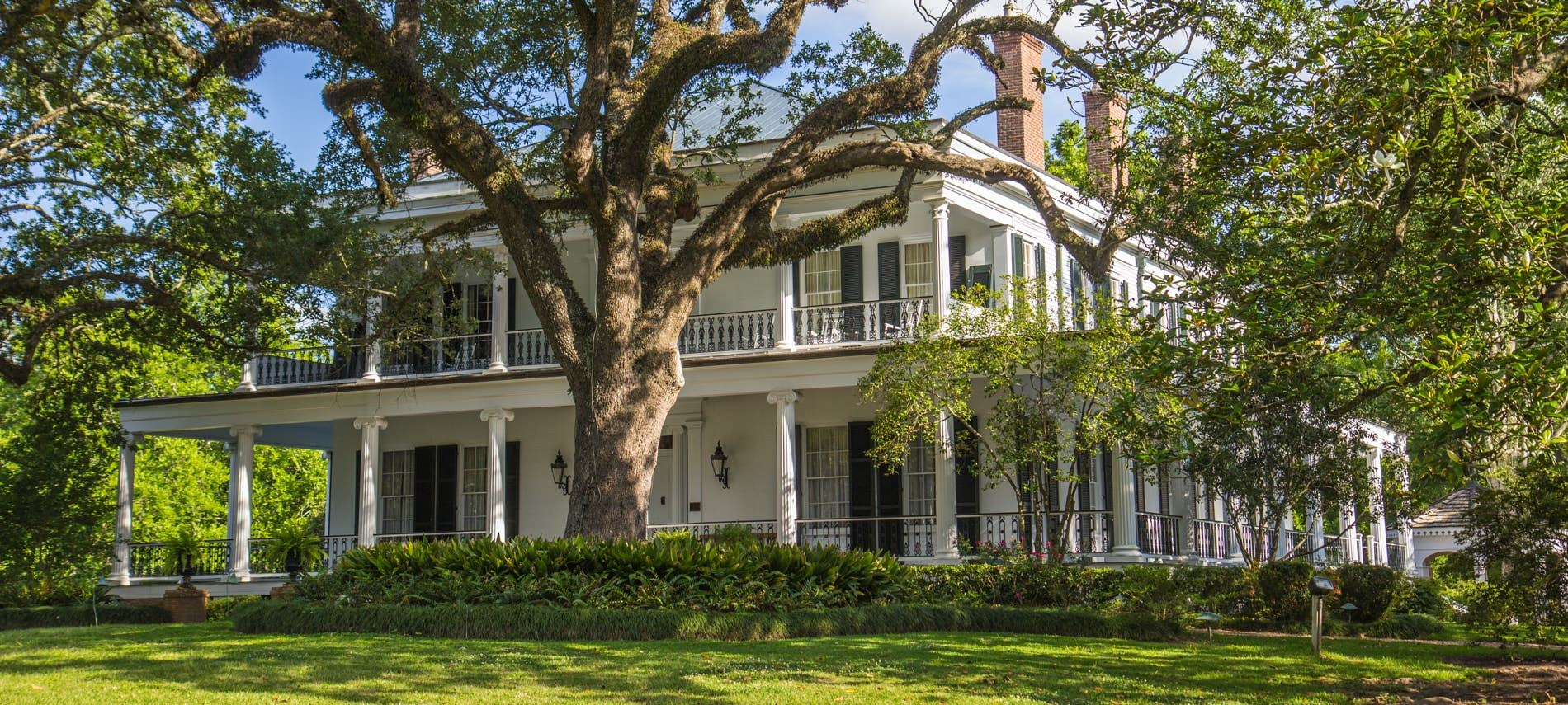 Angled view of two story white b&b with white pillars and black shutters surrounding many windows; trees surround b&b