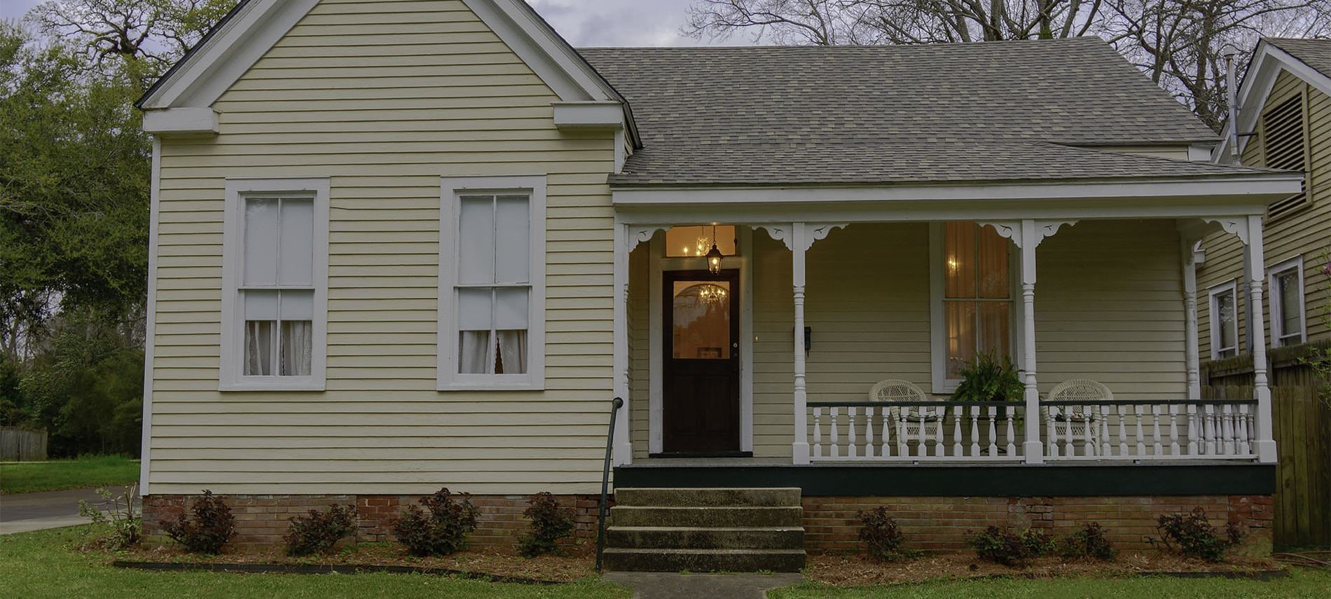 View of b&b porch with dark wood door, cream wicker furniture, cream siding and white trim with small bushes lining yard