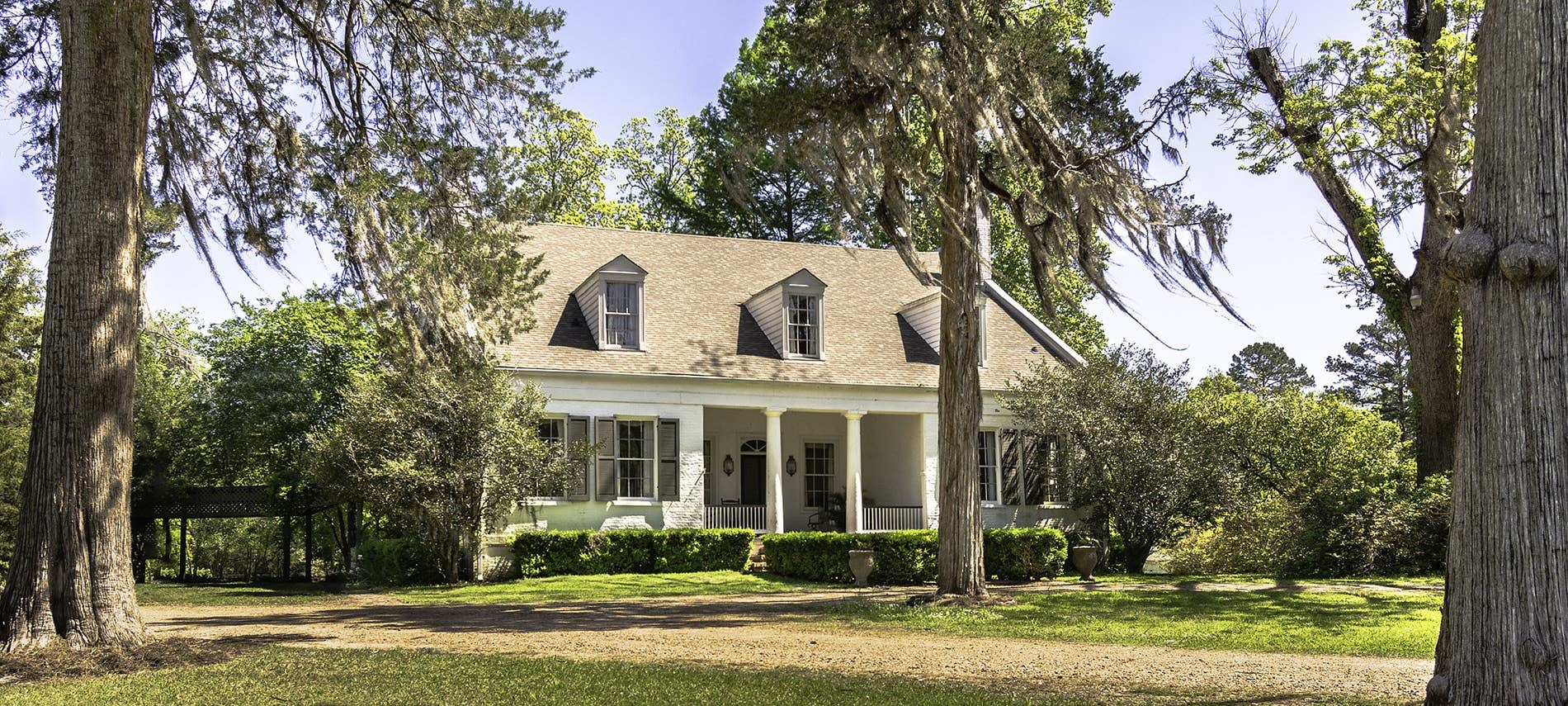 Front view of b&b with white siding and nine windows, a large green lawn with dirt driveway, and area surrounded by trees