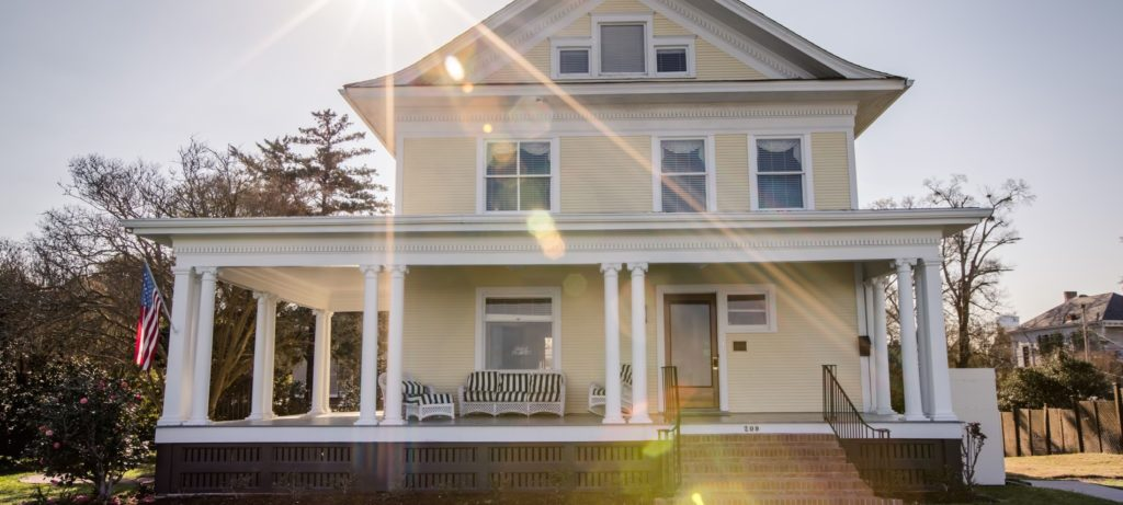 Sun rays over front of b&b with pale yellow siding, white trim and white pillars, many different sized windows, and a brick staircase leading to front porch