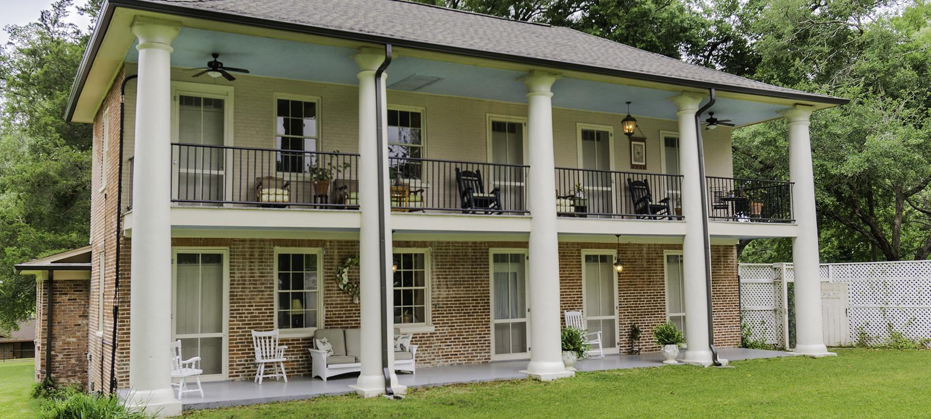 Rear view of the b&b with wide open porch spaces, various chairs and plants, and many windows with a green lawn