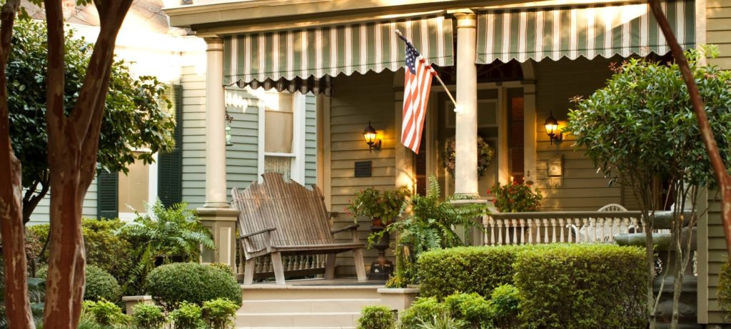 View of front porch covered in ferns and greenery, a rustic bench and furniture, and tan house siding