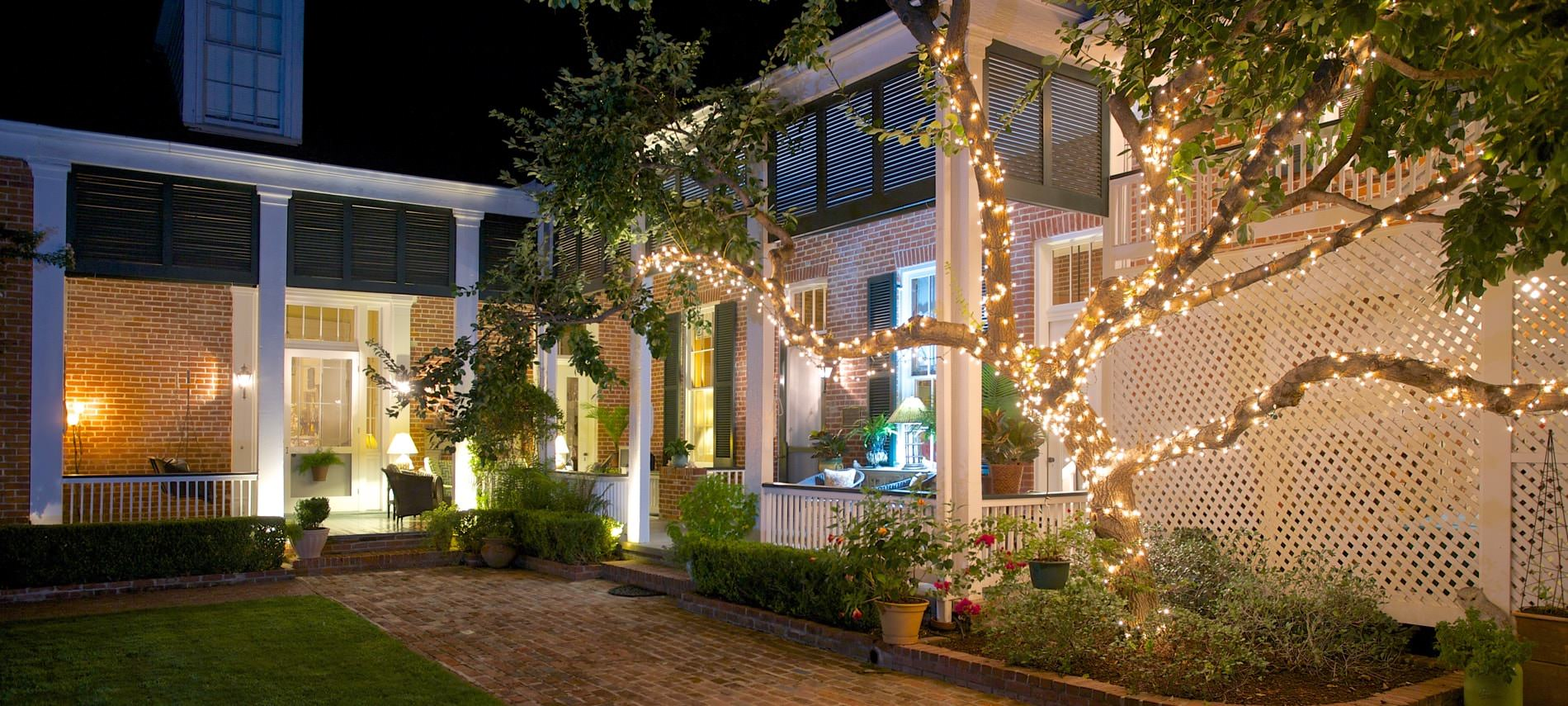 Nighttime view of brick walkway leading to well-lit porch and a tree wrapped in pretty string lights