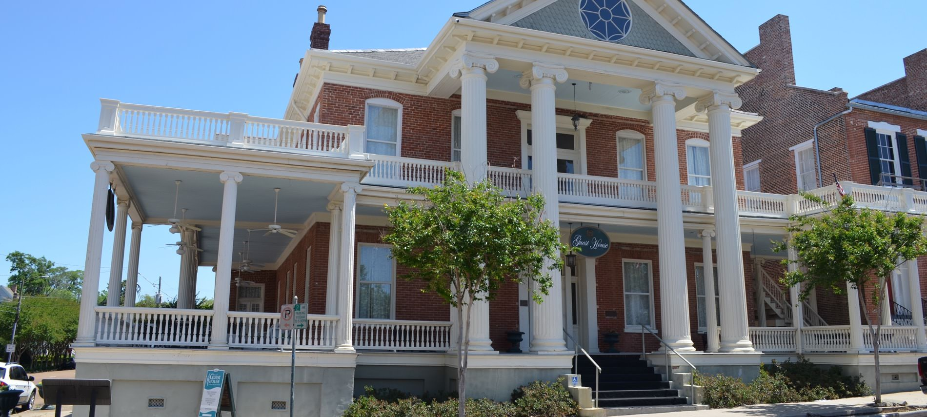 Front view of Guest House that is two stories and covered in red-brick. Has many white pillars, large porch areas, and small trees on front sidewalk