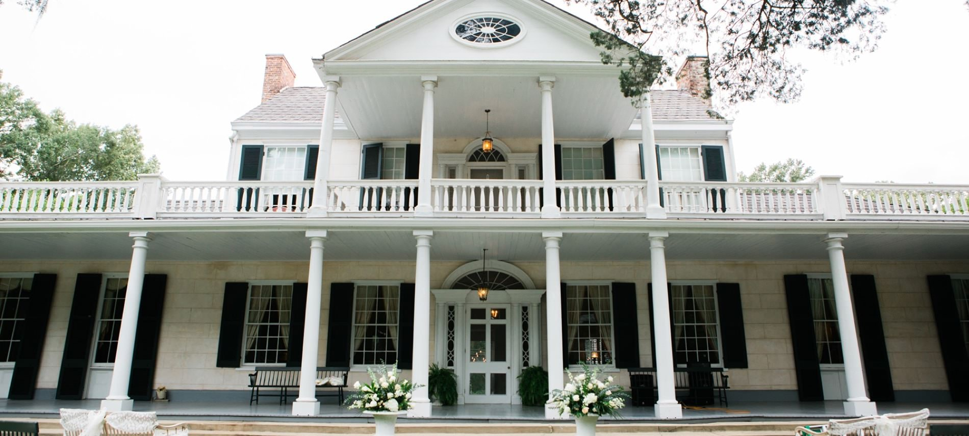 Front view of two story b&b with white stone siding, dark shutters around many windows, white pillars, and intricate white front door