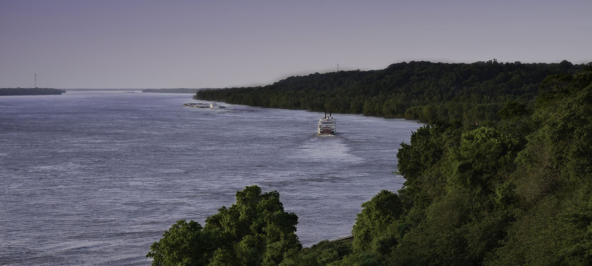 View of trees lining the shore of a lake with a ferry boat riding down the water on a cloudy day