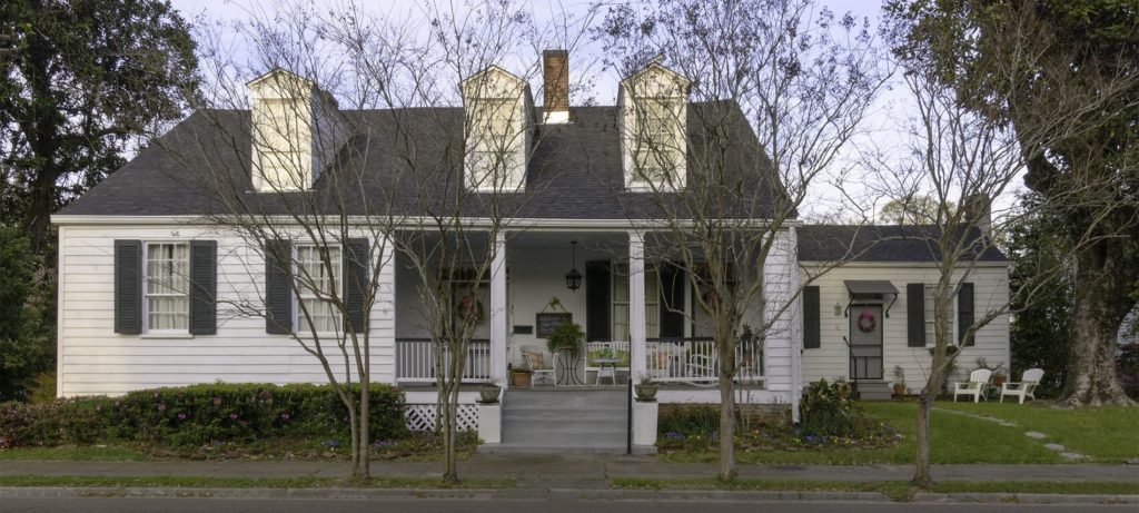 Front view of b&b with white siding, dark gray shutters around windows, lovely front porch with furniture, and three two-story windows