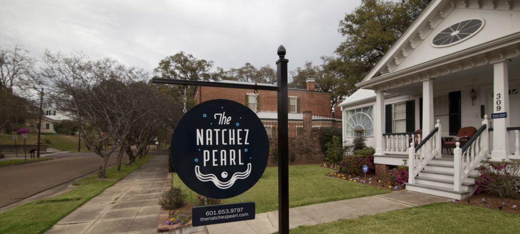 "Black, circular sign reading ""The Natchez Pearl"" in front yard of a white house with stairs leading to the porch on a cloudy day"
