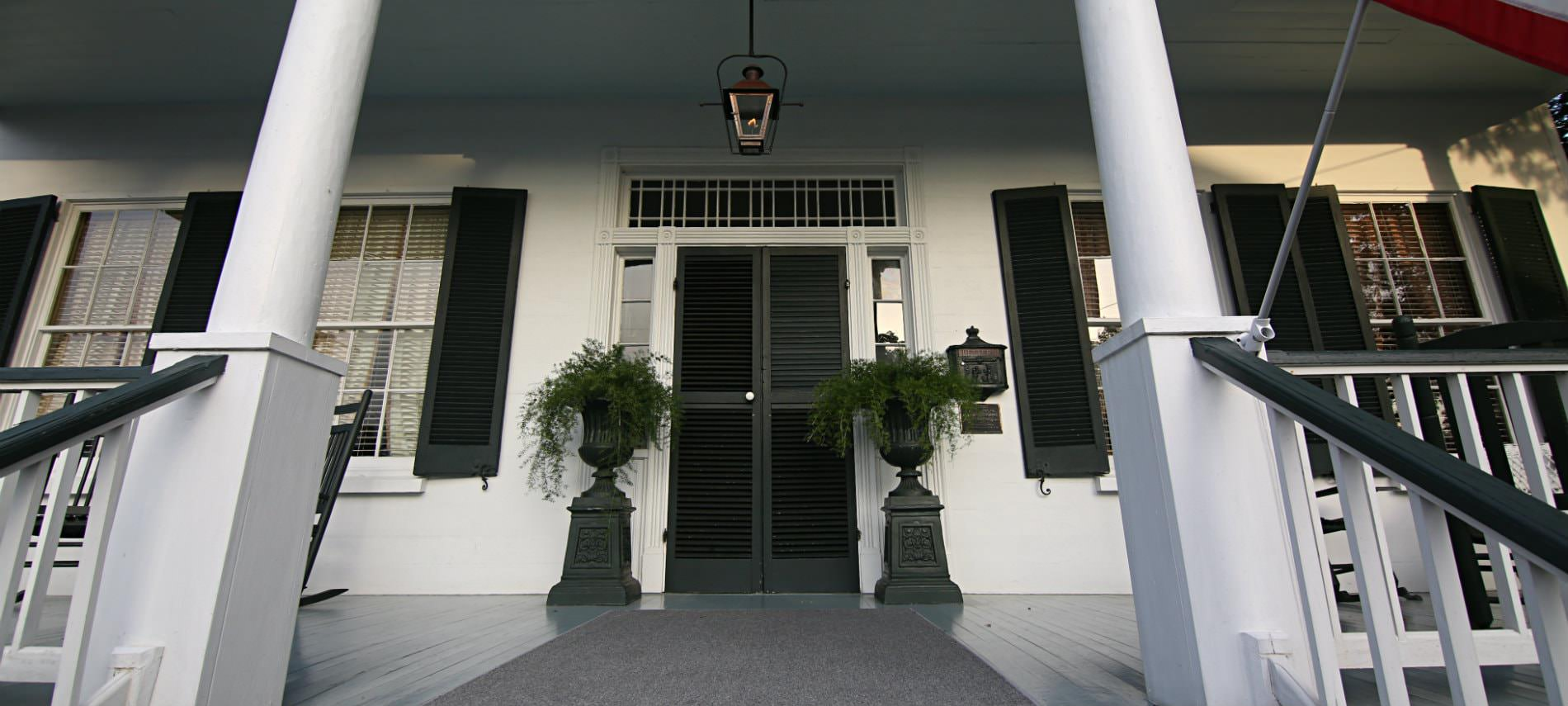 White colonial home with black shutters and front door with two black pedestials holding greenery