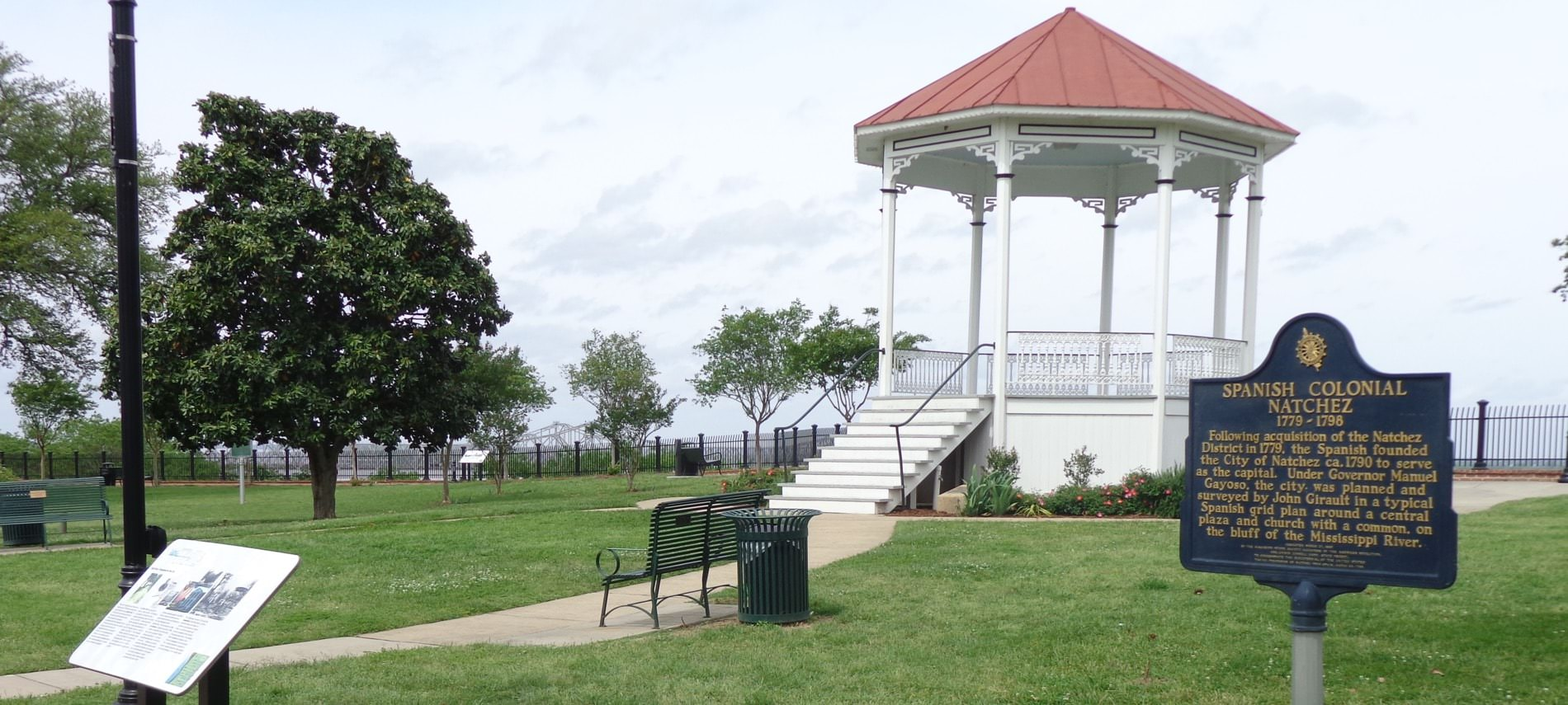 A white gazebo with a red roof overlooking a nice green park with park benches and a pale blue sky