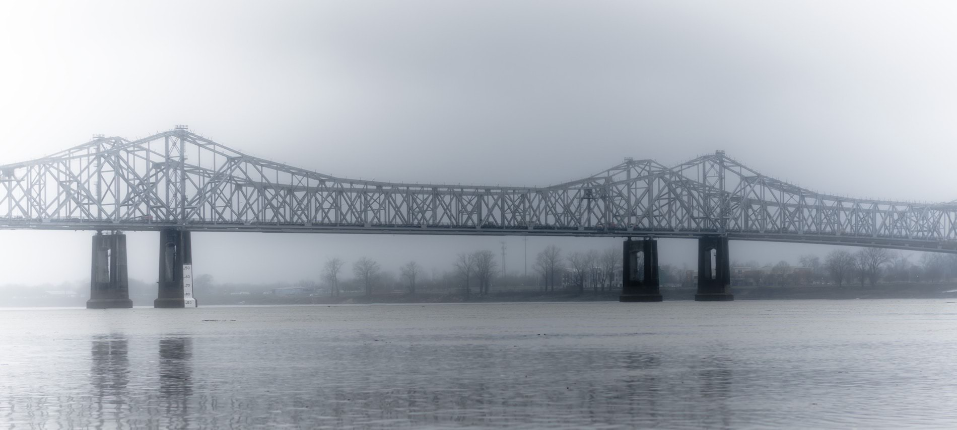 Long driving bridge over the water on a foggy day with bare trees lining the shore in the background