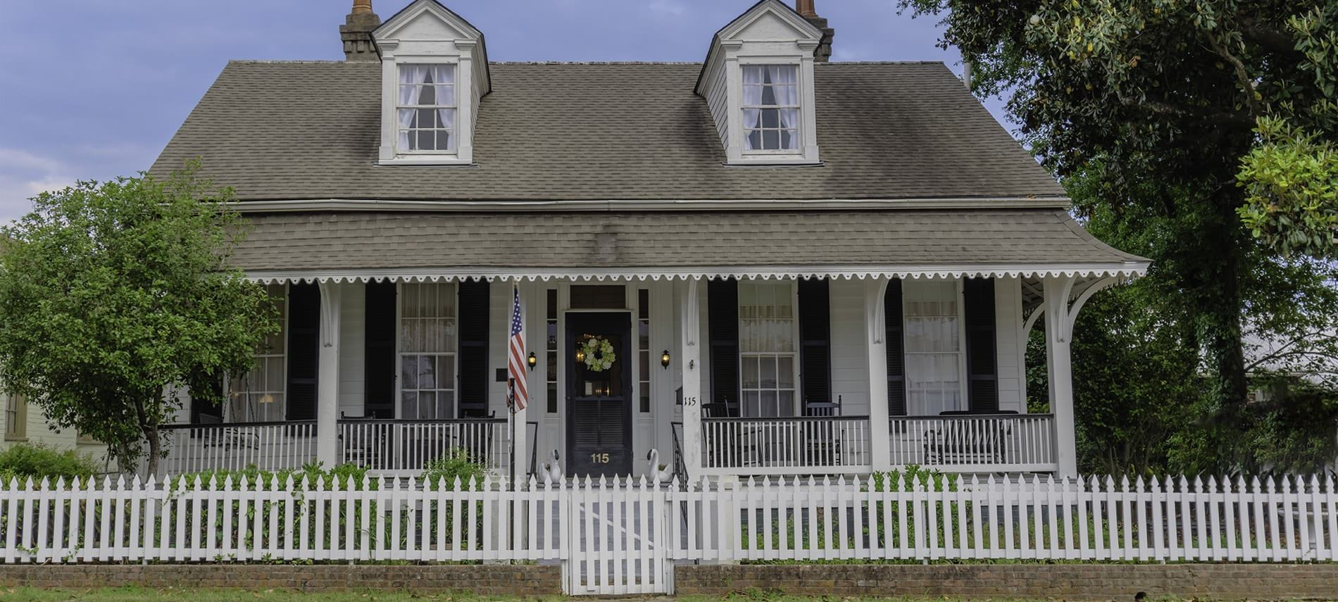 Front view of b&b with short, white fencing, white siding on house with black shuttered windows and front door, slanted roof with two windows, and trees surrounding house