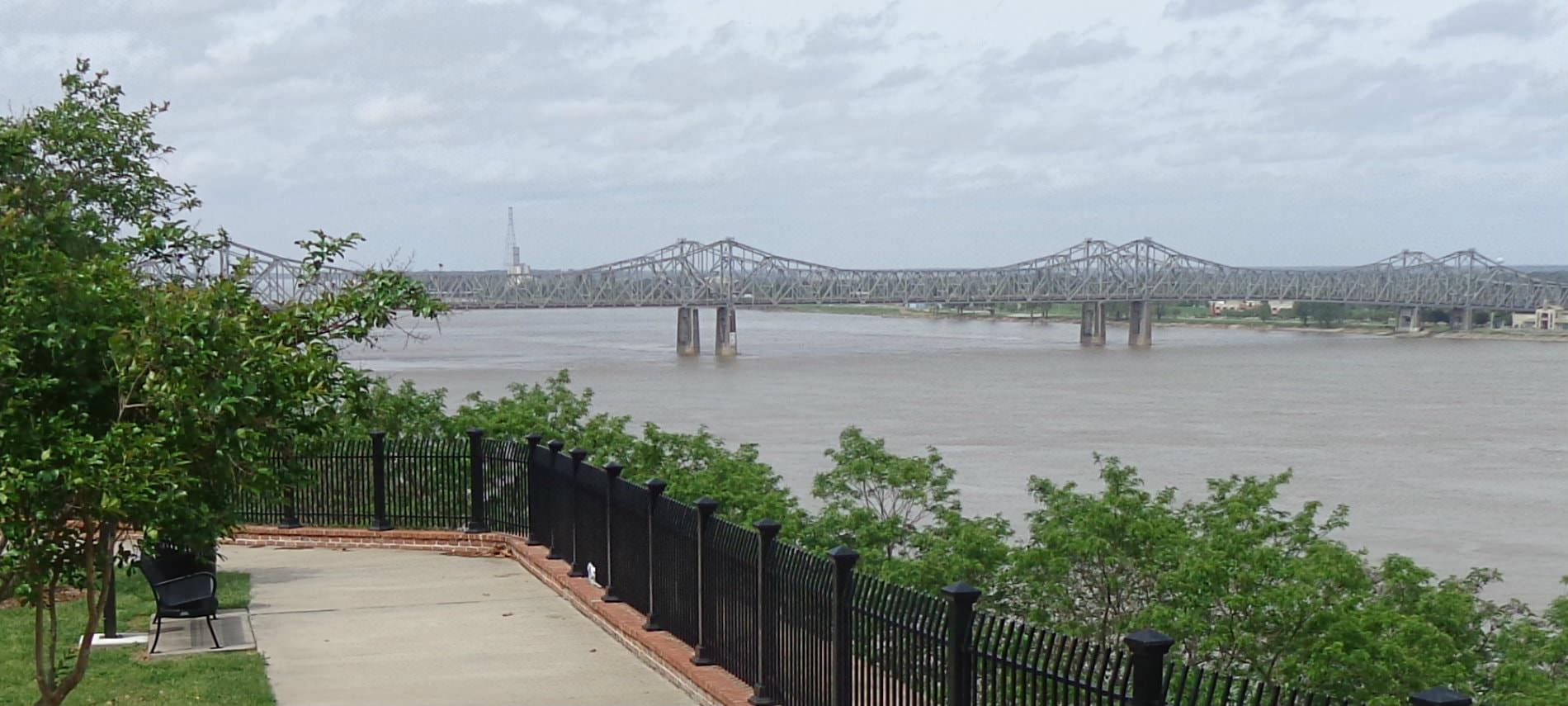 View of a sidwalk in the park overlooking water on a cloudy day and a long bridge in the distance