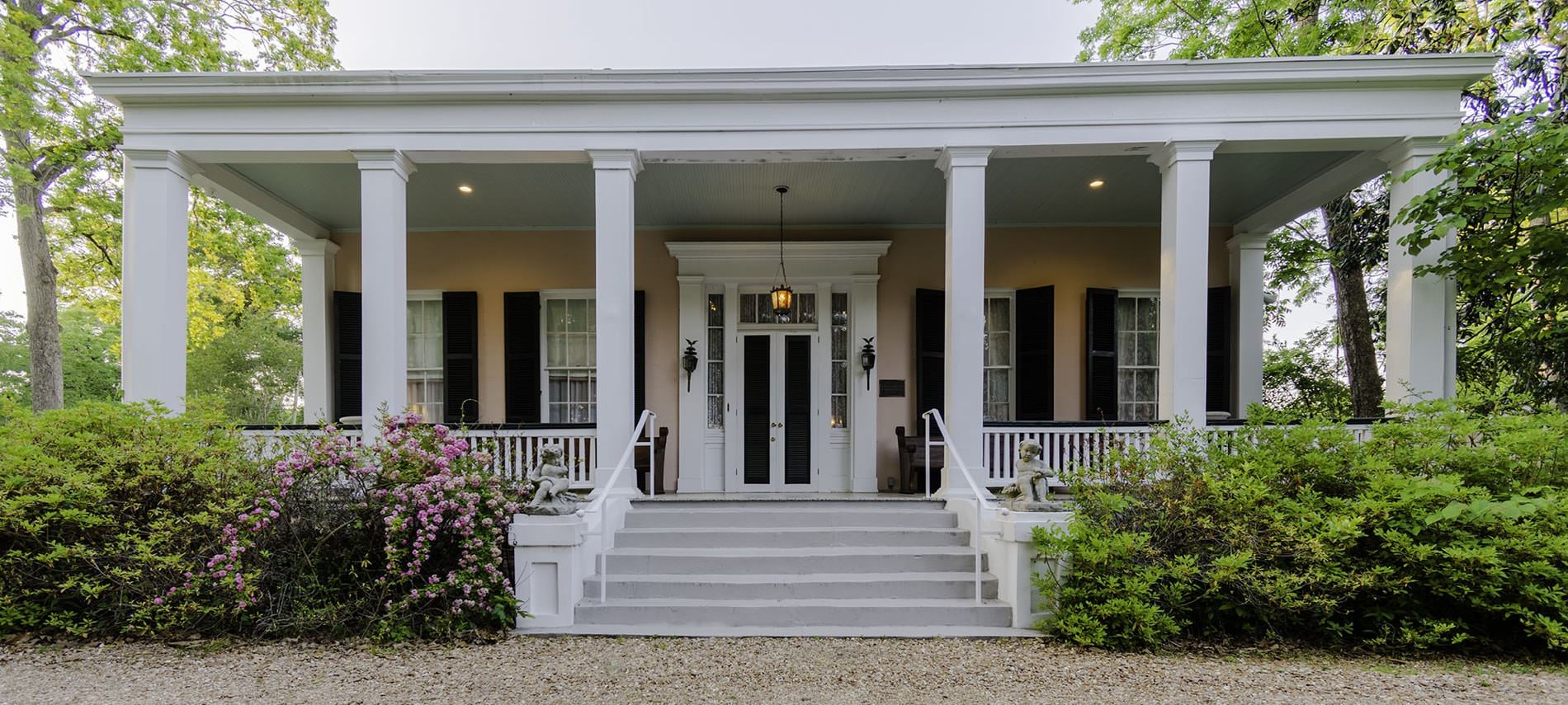 Front view of b&b with light tan siding, white and black windows and front door with white pillars and bushes lining full porch