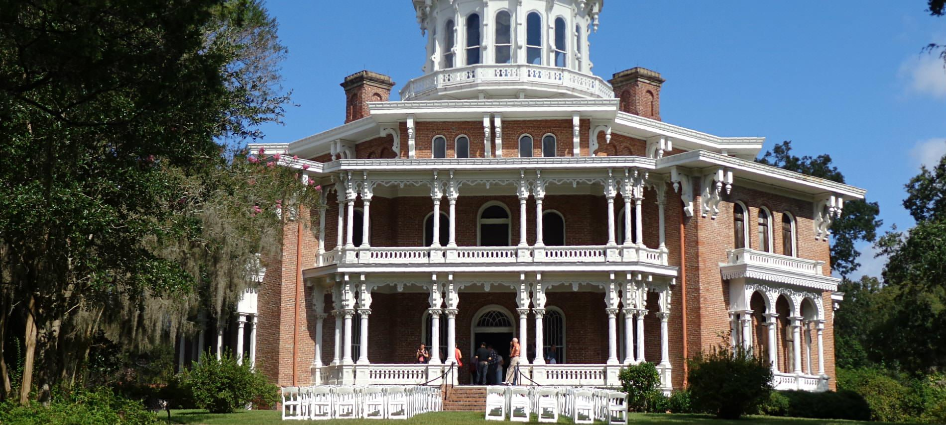 View of a three story brick venue with decorative white pillars and fencing with white chairs in rows in front yard