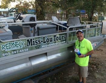 Man standing in front of pontoon boat with Miss-Lou Tours sign