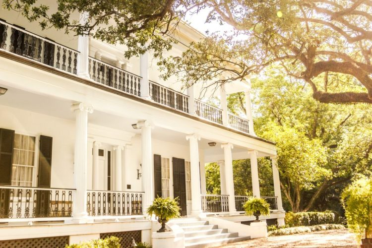 Sunny angled view of front of b&b that is white with black shutters surrounding many windows, white pillars, and a long front porch; trees line background