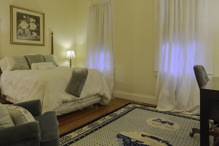 Bedroom decorated with a tall bed covered in a white comforter, pale cream walls, wood panel flooring, a blue and cream rug, and dark wood desk