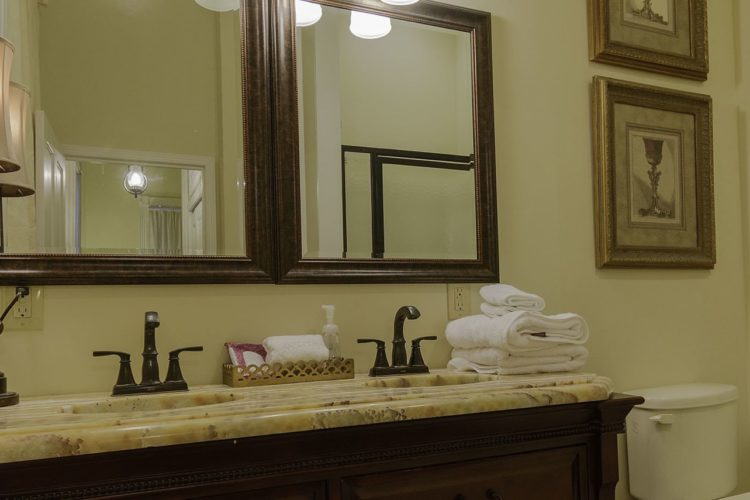 Pale yellow bathroom with yellow granite counter and two sinks, a toilet, and dark wood mirrors