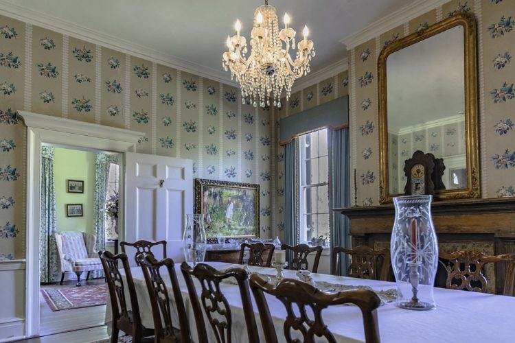 Dining area decorated with a long dining table covered in white tablecloth, many wooden chairs, a wooden fireplace, and beige, blue, and white flowered wallpaper