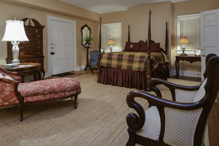 Large bedroom decorated with a tall bed with wood posts and plaid comforter, a red designer fainting couch, and tan walls and carpet over wood flooring