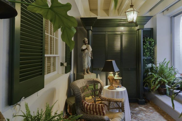 Side view of porch decorated with pale wicker furniture, dark green shutter closet, and many ferns and potted plants
