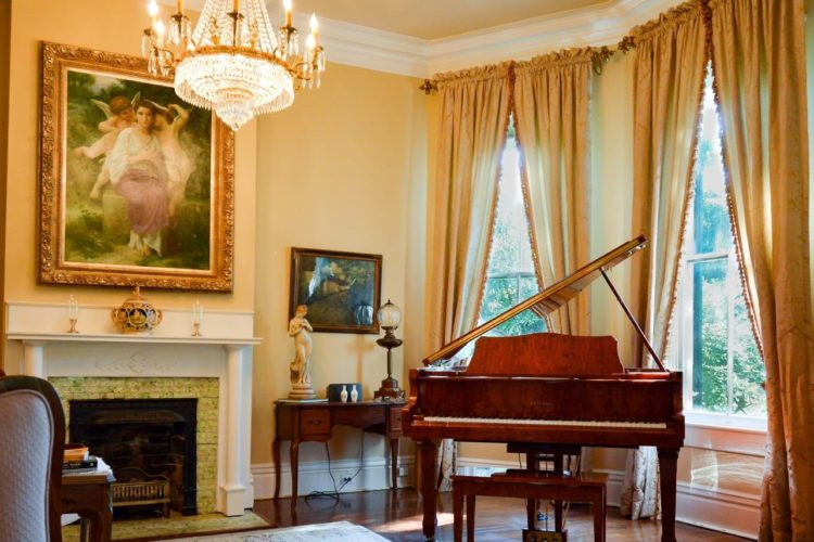 Sitting area decorated with light orange walls, golden curtains and picture frames, a dark redwood baby grand piano, fireplace, and wood flooring