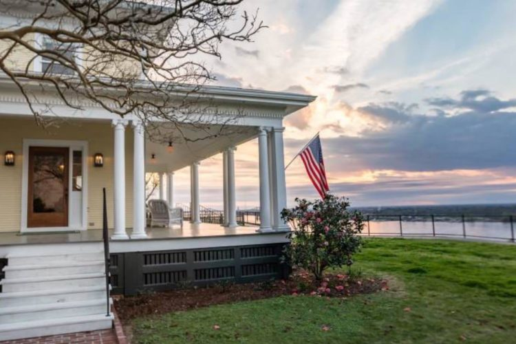Outdoor side view of b&b with pale yellow siding and white trim with white pillars, a green lawn, and water view with a beautiful setting sun