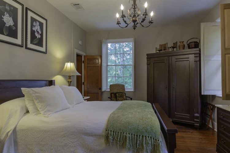 Side view of a bedroom decorated with a large bed with a white bedspread and green throw blanket, dark wooden dressers, and two bedstands with lamps