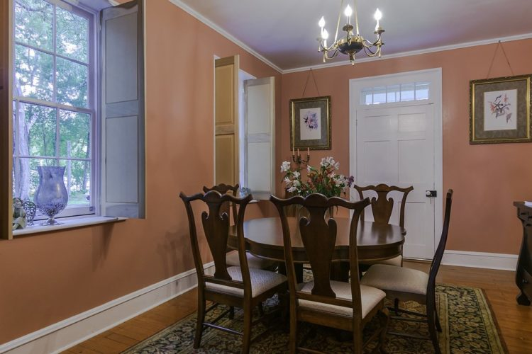 View of dining area decorated with dark wood furniture and cabinetry, salmon walls, wood flooring and a flower patterned rug, and two windows and one door