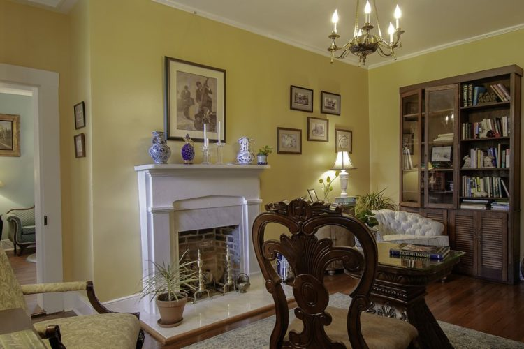 View of sitting area decorated with lemon yellow walls, tan and beige chairs, a white and brick fireplace, wood flooring, and a rustic bookshelf