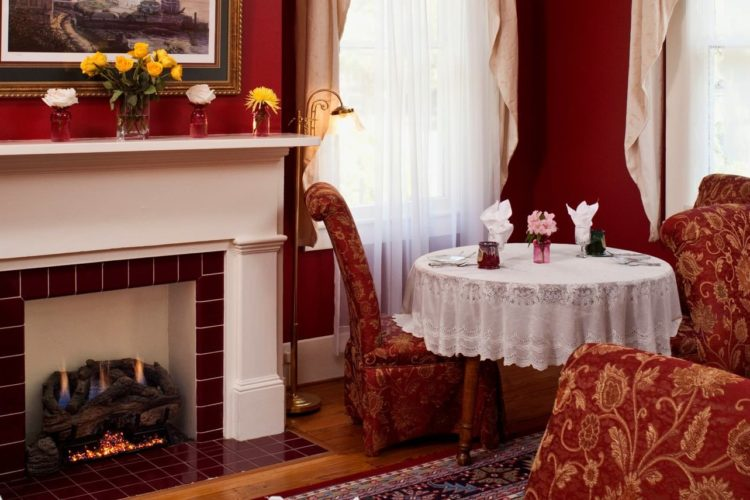 Sitting area decorated with crimson red walls, red and gold patterned chairs, a white and red tiled fireplace, and white lace tablecloth over round table