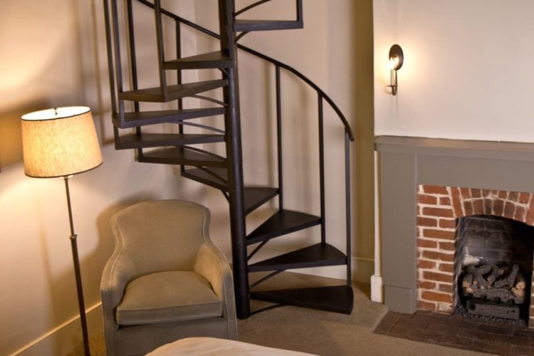 Sitting area decorated with cream walls, a warm gray chair and brick fireplace, and dark brown spiral staircase in the back corner