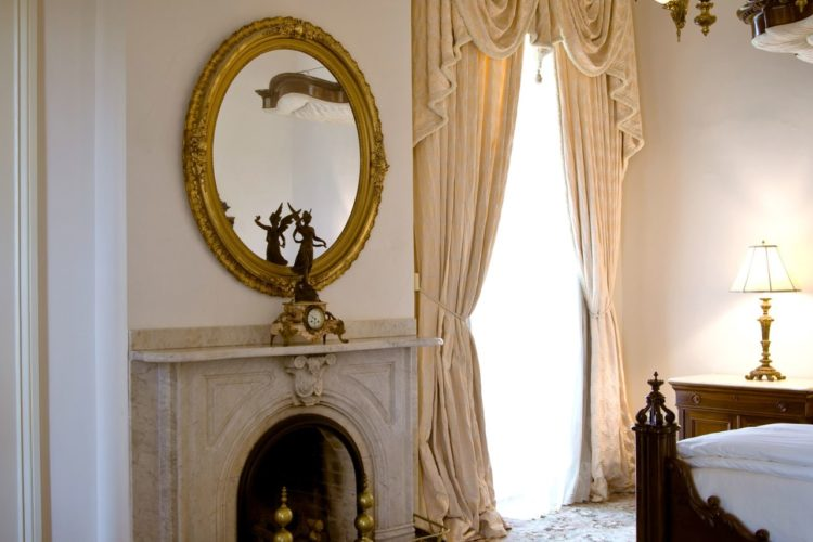 Side view of a bedroom depicting a tall window with cream curtains, a marble granite fireplace, a golden oval mirror, and white walls