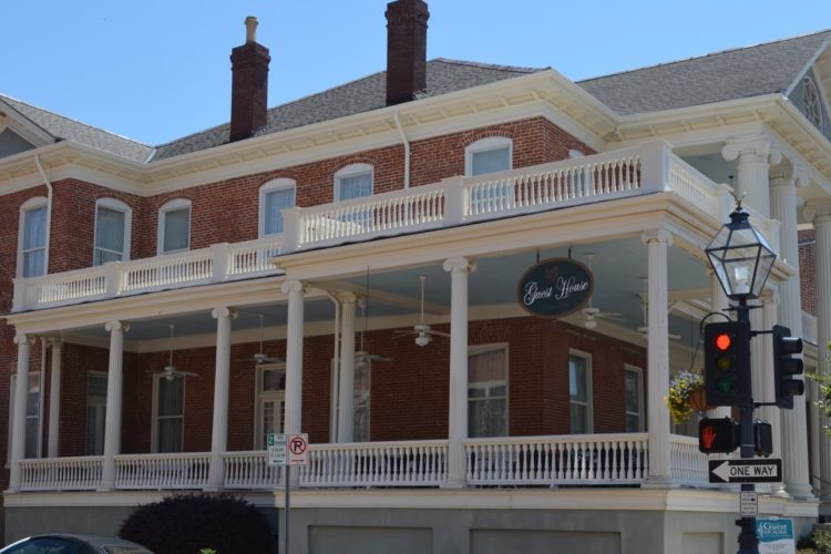 Street view of large, two-story guest house with white pillars and red brick siding surrounded by large porch areas