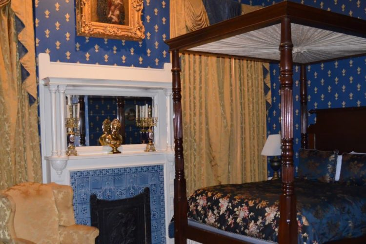 Intricate bedroom with royal blue and gold accented wallpaper, blue-tiled fireplace, silk navy blue and pink-flowered bedspread on poster bed, and golden curtains and chairs