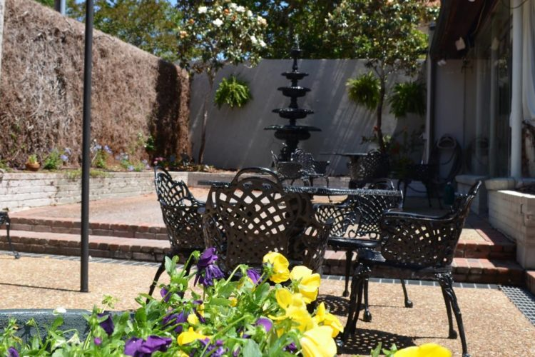 Outdoor seating area with black porch furniture, purple and yellow flowers, tall black water fountain in background and walled in with trees behind