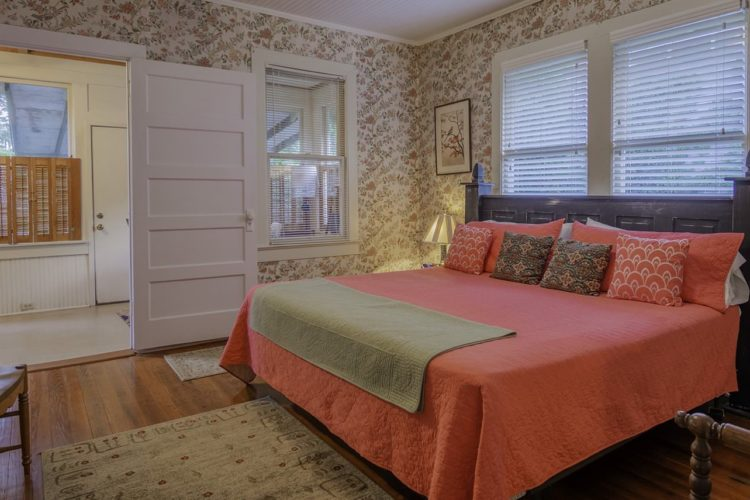 Country inspired bedroom with flower printed cream wallpaper, king sized bed covered in orange quilt and throw pillows, wood flooring and beige rug