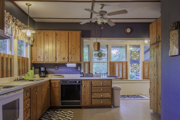 Kitchen area with blue and white polka-dotted wallpaper, cabin-inspired wooden cabinets and pantry, and white stove and many windows