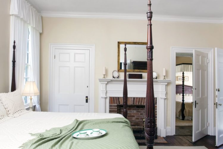 Cottage style bedroom decorated with eggshell walls, dark wood flooring, a king-sized bed with white linens and green throw blanket, a brick fireplace, and three white doors