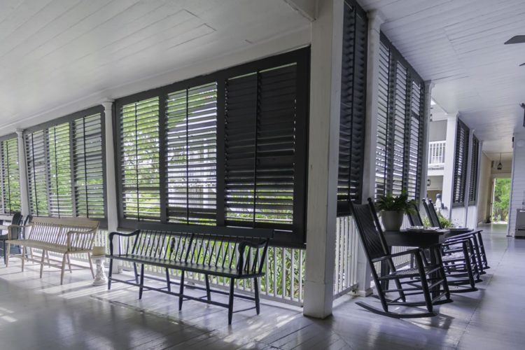 Large covered porch area painted bright white with black shutters for weather protection, multiple benches and rocking chairs overlooking greenery