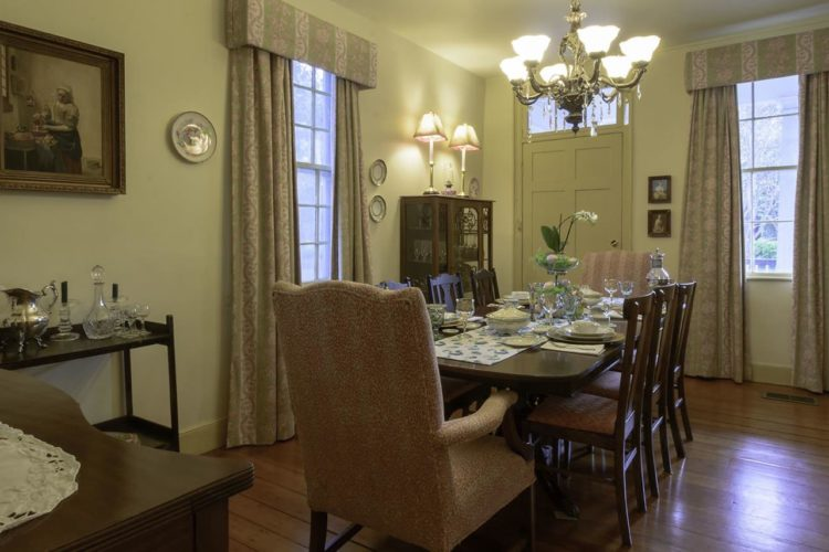 Dining room with pale yellow walls, wood flooring, dark wood dining table with eight chairs, two large windows and one door, and dish cabinet against wall