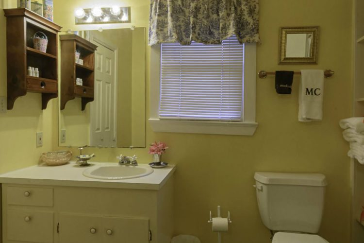 Bright lemon yellow bathroom with towel shelf, toilet, sink with drawers, another closed door, and single window