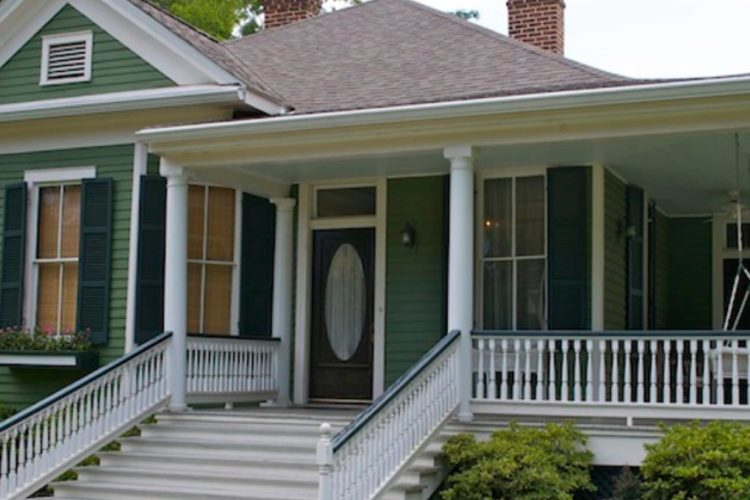 Front view of single story forest green b&b with white pillars, porch, and trimming; green trees and grass surrounding outside